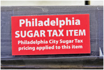 A sticker alerting customers of the sugar tax posted by sweetened beverages.
