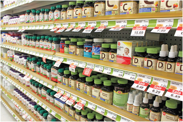 Different types of vitamins and supplements on shelves in a pharmacy. According to studies, North America and Asia lead vitamin and supplement usage in the world.