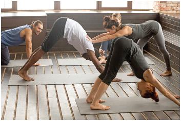 A Hatha yoga fitness instructor teacher helping a beginner.