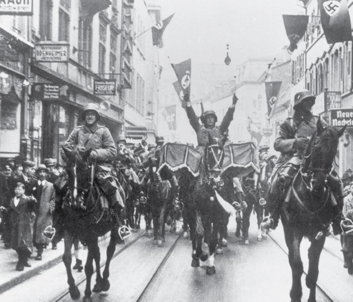 Mounted German troops ride down a street in Heidelberg after Germany retook the Rhineland.