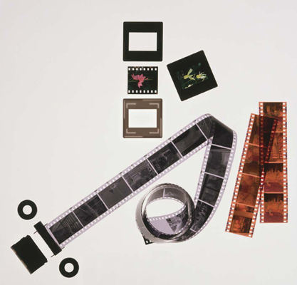 Pictured in this photograph are a roll of black-and-white film, strips of coloured negative film, and coloured slides in and out of their cases