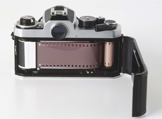 An opened back of a 35-mm camera reveals a loaded roll of film that is perforated and uses a transport sprocket to draw the film from a cartridge onto another spool as it advances from picture to picture