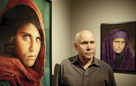 Steve McCurry poses next to his acclaimed photograph Afghan Girl at an exhibition of his work in Germany in 2013.