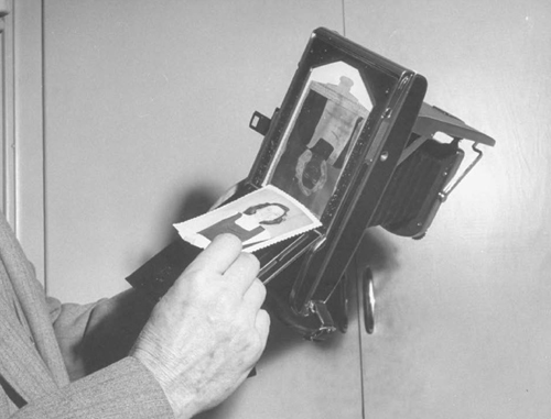 This person is removing an instantly developed photograph from a Polaroid camera in 1948.