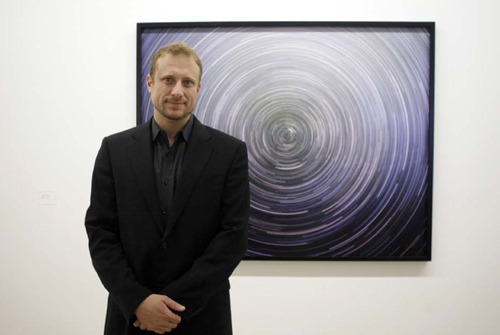 Trevor Paglen poses in front of one of his astrophotographs at a 2009 exhibition in Germany. Paglen uses cameras mounted on high-powered astronomical telescopes with focal lengths up to 7000mm.