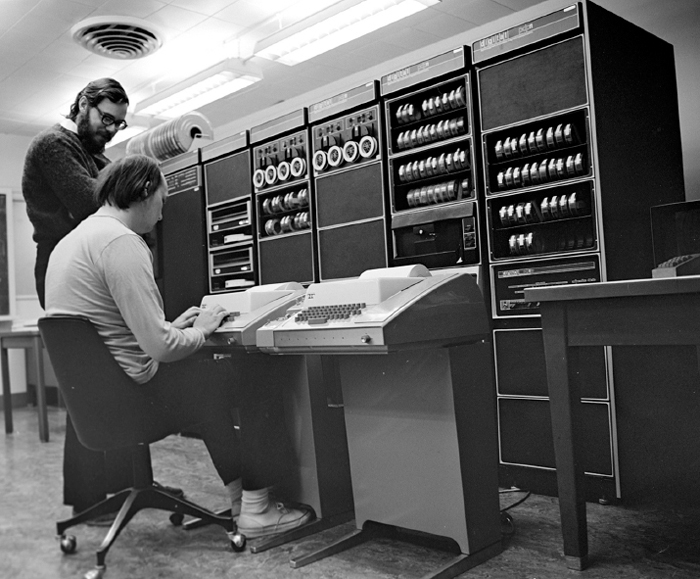The creators of UNIX were Dennis Ritchie (standing) and Ken Thompson (sitting). By Peter Hamer, CC BY-SA 2.0 (http://creativecommons.org/licenses/by-sa/2.0), via Wikimedia Commons.
