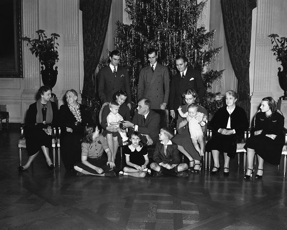 """It was a family Christmas at the White House in Washington on Dec. 25, 1939 for the Roosevelts and above is the family portrait in the East Room. Only the families of Elliott and James Roosevelt were missing. Seated on floor, left to right: Eleanor """"Sistie"""" Dall; Diana Hopkins, daughter of Harry Hopkins, secretary of commerce; and Curtis """"Buzzie"""" Dall, Jr. Seated, left to right: Mrs. Eleanor Roosevelt; Mrs. Sara Roosevelt, the president's mother; Mrs. Franklin Roosevelt, Jr., with Franklin III on lap; the president; Mrs. John Boettiger, the president's daughter, Anna, holding her son, Johnny; Mrs. J.R. Roosevelt, the chief executive's sister-in-law; and Mrs. John Roosevelt. Standing, left to right: Franklin, Jr., John Roosevelt and John Boettiger."""