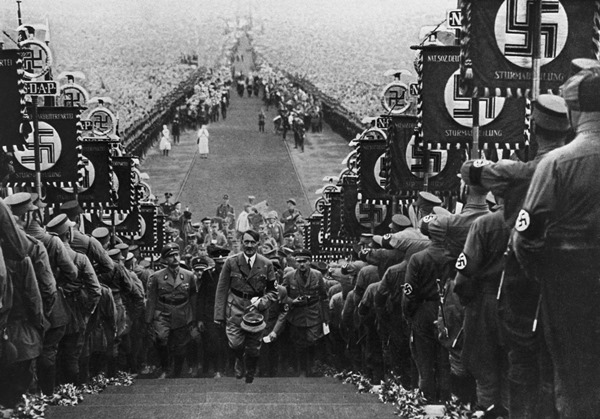 Adolf Hitler, German dictator, ascending the steps at Buckeberg flanked by banner-carrying storm troopers who display the Nazi swastika.