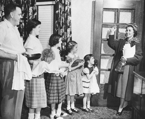 A working mother waves goodbye to her family as she leaves to go to her job outside of the home, 1953.  BETTMANNCORBIS. REPRODUCED BY PERMISSION.
