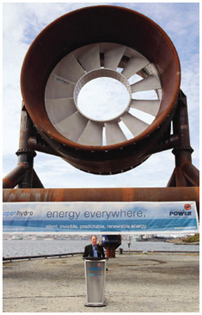 An executive from Nova Scotia Power speaks about the companys tidal power test project while standing in front of a large turbine unit. The turbine was destined for the Bay of Fundy, home of some of the highest tides in the world.