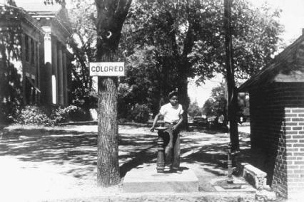 In the highly segregated South, a young girl takes a sip of water from a drinking fountain designated for Colored people only. Separate facilities were common in the South and included schools, modes of transportation, public places like parks