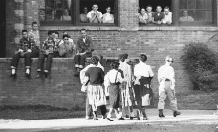 White students watch as a group of black students is escorted by a soldier to Central High School in Little Rock, Arkansas, in 1957.
