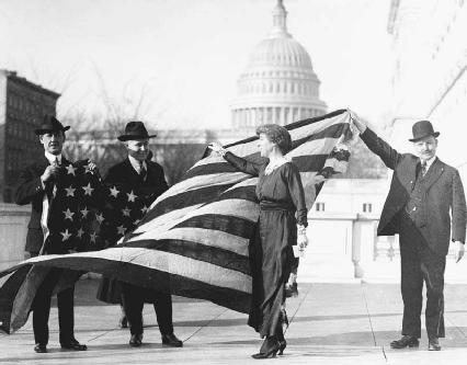 The first woman elected to Congress, Jeannette Rankin is shown receiving the American flag that flew over the House of Representatives when the Nineteenth Amendment was passed in the House.