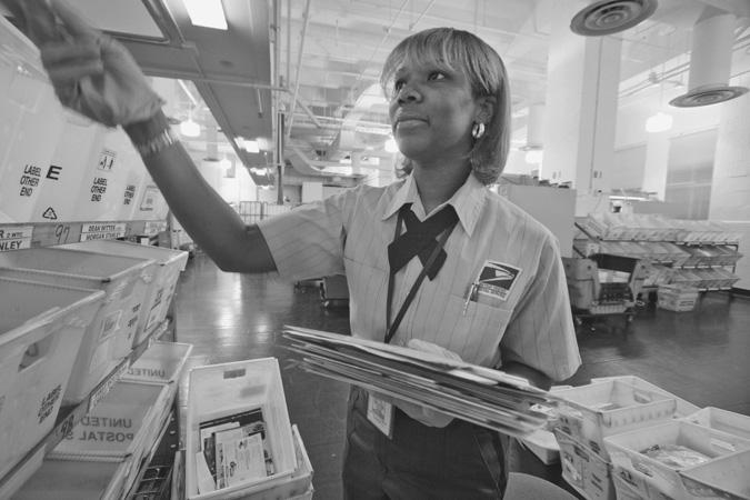 Postal Worker Sorting Mail