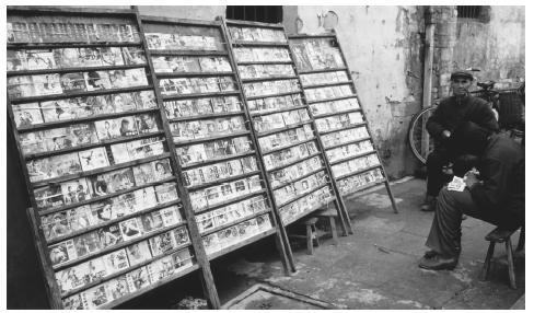 A merchant rents books from a sidewalk rack on a street in Tunxi.