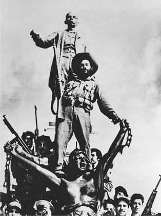 Followers of Fidel Castro posing on a monument in Matanzas, Cuba, 1959. The sculptures are of the leader of the Cuban independence movement Jos Mart and a female allegorical figure of liberty brandishing broken chains.
