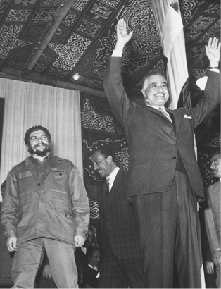 Egyptian President Gamal Abdel Nasser gestures to a crowd as visiting Cuban industry minister Ernesto Che Guevara (left) looks