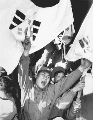 Anticommunist North Koreans wave Republic of Korea (ROK, South Korea) flags as they arrive in Seoul after being released from prisoner of war (POW) camps. The issue of repatriation complicated the armistice negotiations