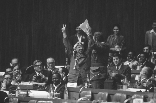 Cuban President Fidel Castro and Palestine Liberation Organization leader Yasir Arafat raise their hands together during a session at the Seventh Summit of the Non-Aligned Movement in New Delhi in March 1983. (Alain NoguesCorbis Sygma)