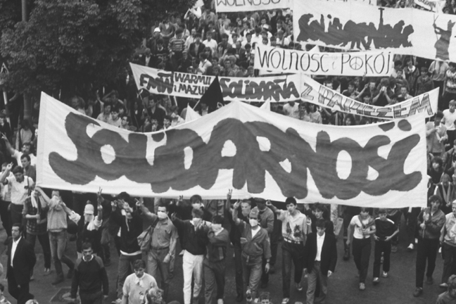 During a 1987 visit to Poland by Pope John Paul II, demonstrators march down a street carrying banners reading Solidarno?? (Solidarity), the name of the first Polish trade union, formed despite communist government opposition.