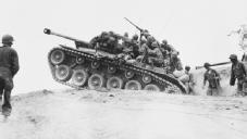 On the Offensive. An American tank crests a hill, followed by U.S. Army troops. NATIONAL ARCHIVES AND RECORDS ADMINISTRATION