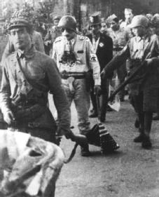 POWs in North Korea. One of the American and South Korean prisoners of war being paraded through the streets of Pyongyang on 3 October 1950 is forced to dress as Adolf Hitler and to drag an American flag on the ground. ARCHIVE PHOTOS, INC.
