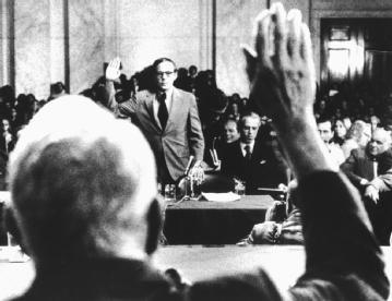 John Dean. The fired White House counsel (background) is sworn in by Senator Sam Ervin, the colorful Senate Watergate committee chairman, on 25 June 1973, before the start of five days of testimony that proved devastating to the president. © CORBIS