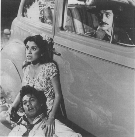 During the brawl at Sleepy Lagoon, Della (Rose Portillo) comforts a badly beaten Henry (Daniel Valdez, the playwrights brother) while El Pachuco (Edward James Olmos) watches from the car