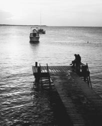 A couple sitting on the docks at Captain Dons Habitat, Bonaire, Netherlands Antilles