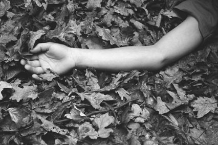 Childs arm lying in leaves