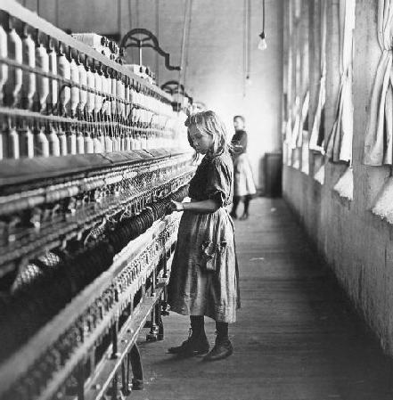 A young girl operates a spinning machine.