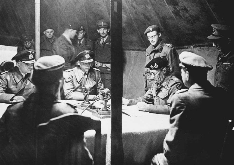 German delegates listen as British field marshall Bernard Montgomery reads the terms for their surrender, May 1945. Left to right around the table: Major Friedal, Kontur Admiral Wagener, Commanding Admiral Hans Georg Friedeburg, Field Marshall Montgomery, General of the Infantry Eberhard Kinzel, Colonel Fritz Poleck. © BETTMANN/CORBIS