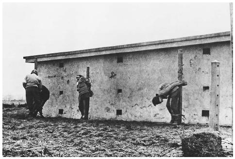 An American medical officer examines the bullet-riddled bodies of three German spies who died before a U.S. firing squad in Herbesthal, Belgium, in December 1944. ©BETTMANN/CORBIS.
