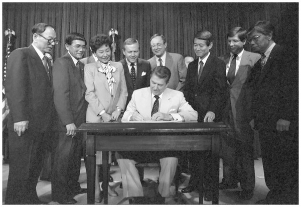 President Ronald Reagan, despite his initial opposition, signs the 1988 Civil Liberties Act that authorized redress and reparations for the internment of Japanese Americans during World War II. (Ronald Reagan Library)