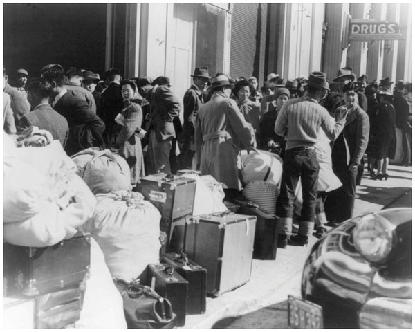Japanese Americans report to the San Francisco Wartime Civil Control Administrations station in January 1942. Piled on the sidewalk are their belongings. (Getty Images)