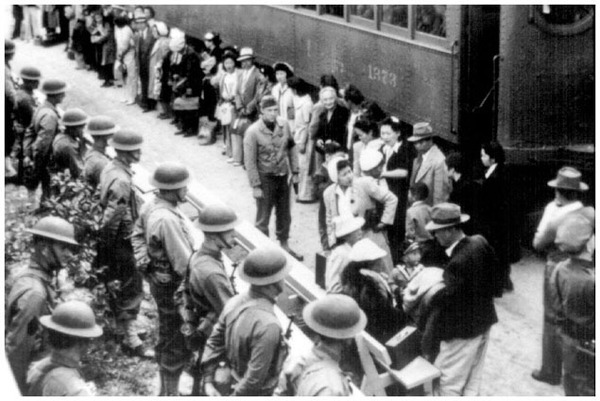 A line of armed soldiers greet Japanese Americans at the Santa Anita Assembly Center, April 5, 1942. (National Archives)