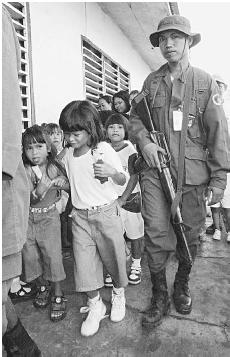A police officer guards children at an elementary school in the southern Philippines in June 2000. Fighting between Muslim separatists and government forces have raised fears about the children's safety. (AFP/CORBIS)