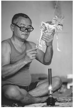 A man in Yogyakarta, Java, making a shadow puppet. (OWEN FRANKEN/CORBIS)