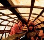 Yupik family beneath an umiaq, a traditional skin boat