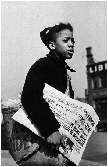 The Chicago Defender, an African-American newspaper, promoted the social and economic promise of the North, thus encouraging African Americans to migrate from the South. This photo, taken in 1942, shows a newsboy selling copies of the paper.