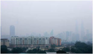 Brush fires send thick haze over Kuala Lumpur, Malaysia, disrupting traffic and triggering health warnings, 2006.