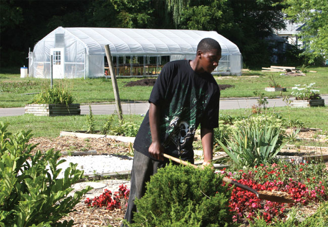 A young person works on an urban farm in Flint, Michigan, as part of the Urban Community Youth Outreach farm.