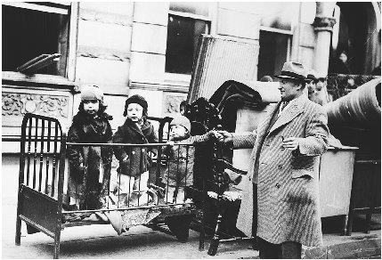 Evicted from their apartment and with their belongings thrown onto the street, these children wait as their parents try to make other living arrangements. Corbis Corporation. Reproduced by permission.
