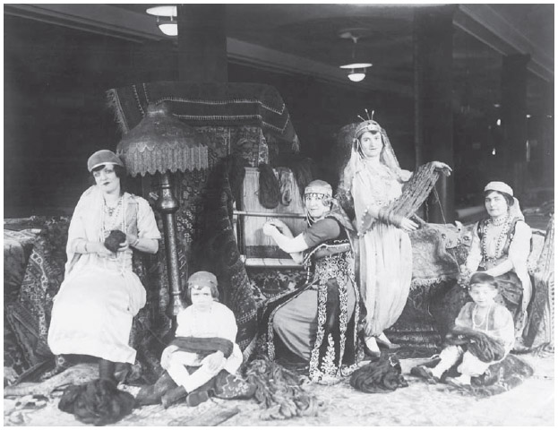 A group of Armenian immigrant women weave a rug on a loom.