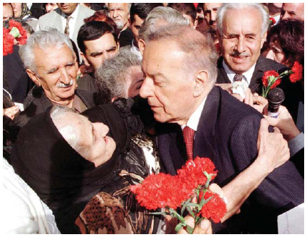 In Cleveland, Ohio, Azeri President Heydar Aliyev (1923–2003) is embraced by an Azerbaijani American woman during his visit to the memorial cemetery of the fighters who had died for the independence of Azerbaijan, in Baku, 1998.