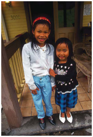 Two Cambodian American girls stand on their front steps in Seattle, Washington, 1994.