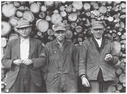 Three French-Canadian farmers stand together outside a potato starch factory.