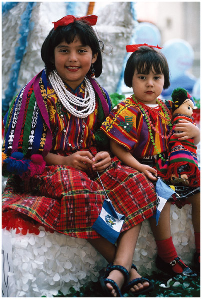 Two young girls wear traditional, hand-woven Guatemalan dresses as they participate in a Central American ethnic pride parade in Chicago, 1995.
