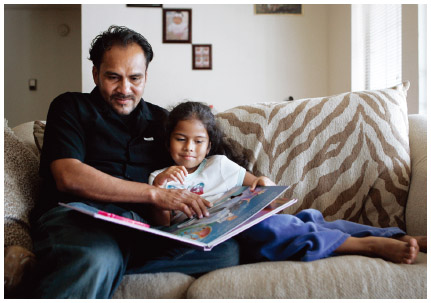 A Honduran immigrant reads to his daughter in their home in Nashville, Tennessee.
