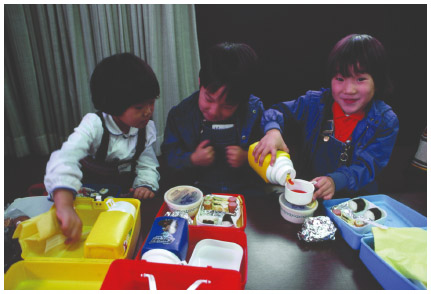 Three Japanese American children eat their bento lunches in 1985. A bento is typically packed in a box-shaped container and includes rice, meat or fish, and pickled or cooked vegetables.